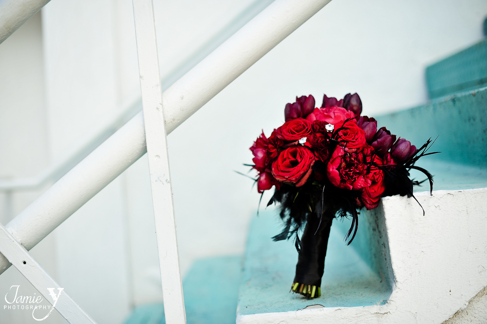 red and black wedding flower bouquet with black feathers