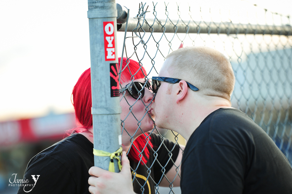 couple kissing through chain link fence
