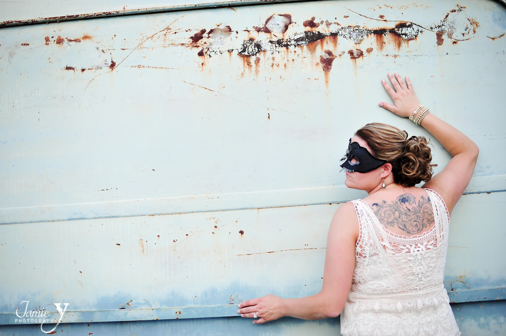 bride wearing a masquerade mask and a tattoo